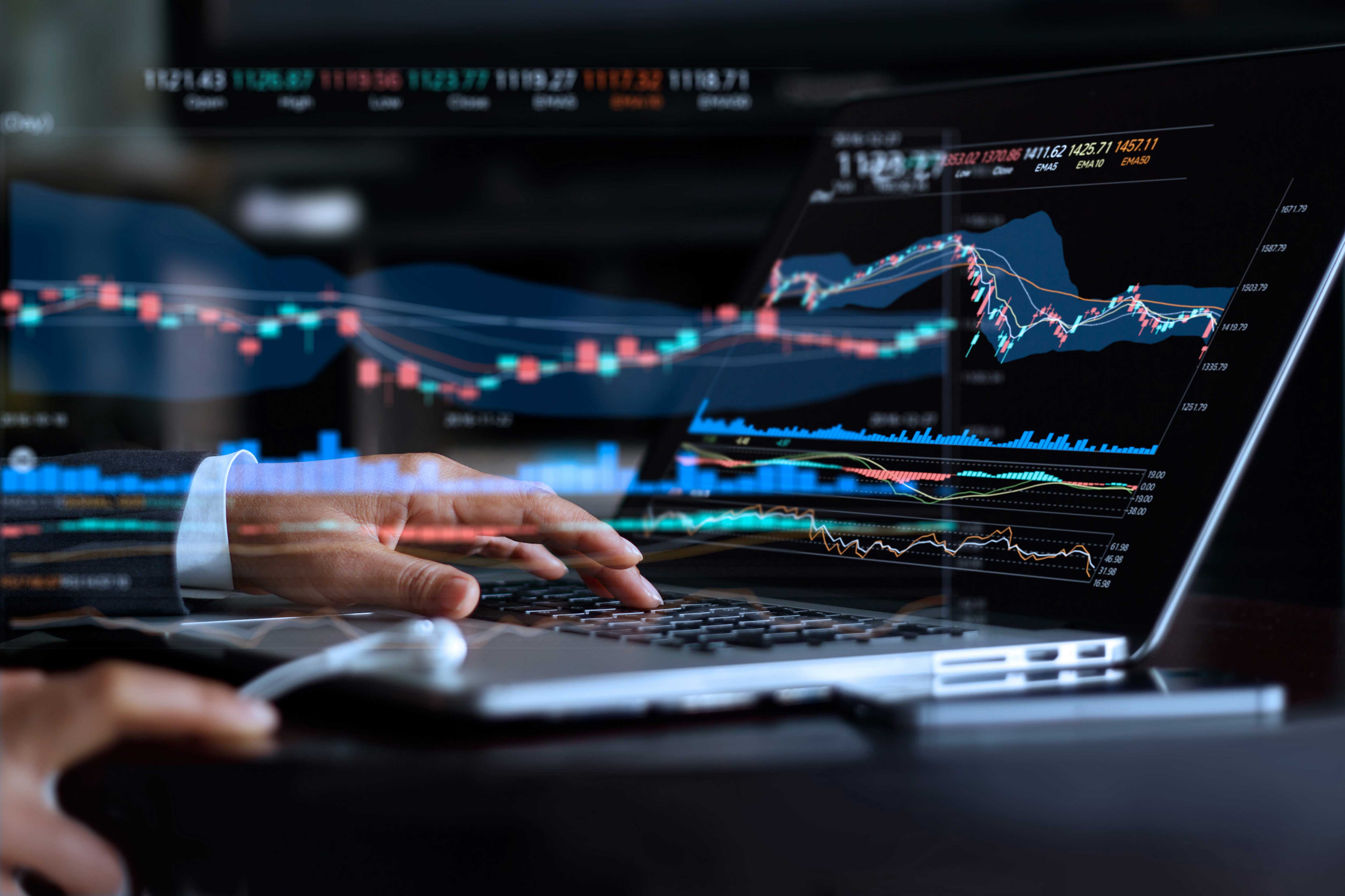 Businessman using laptop to view stock market graph