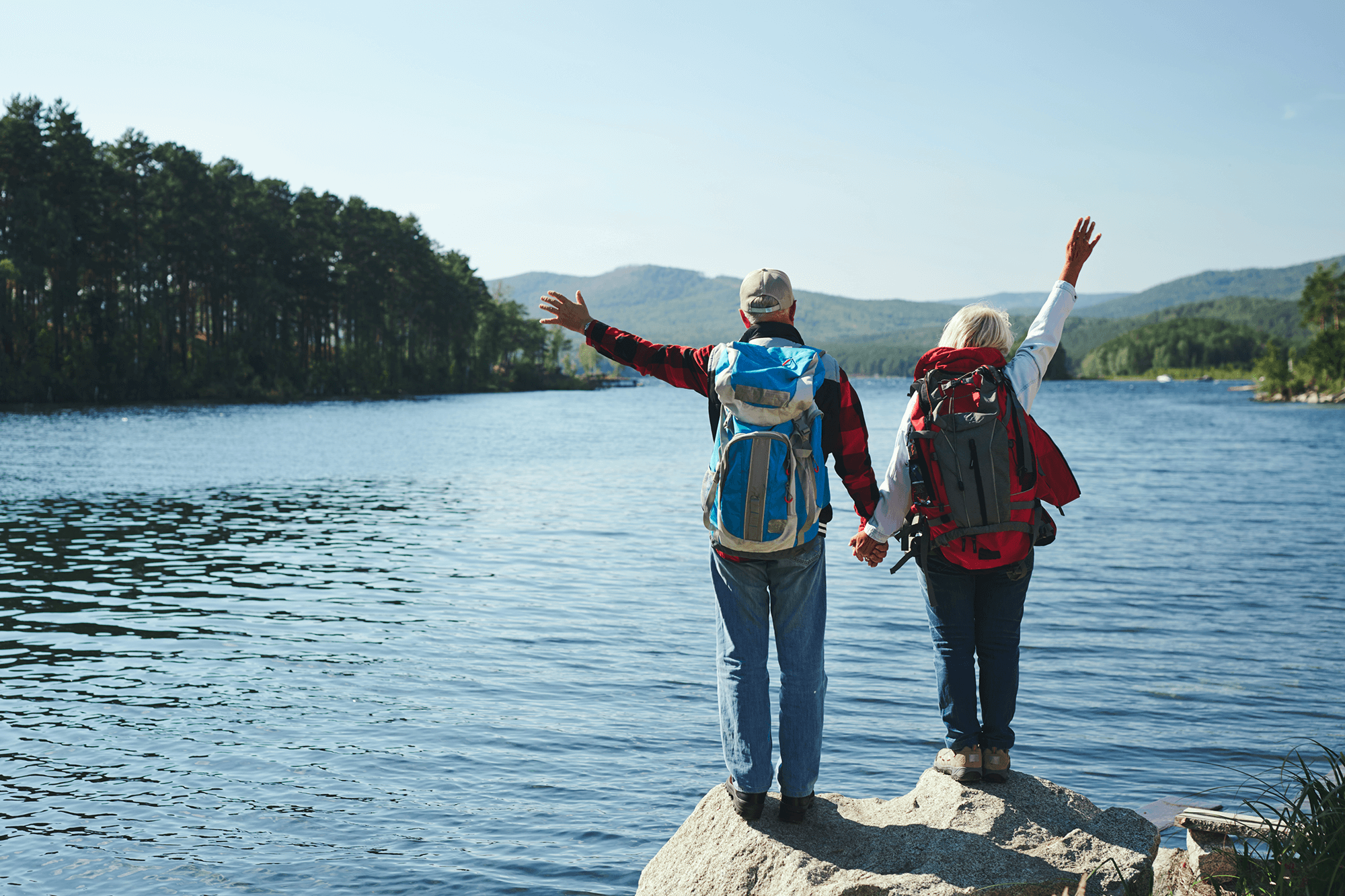 An elderly couple wearing hiking gear stands on a rock overlooking a lake with their back facing the camera and their arms up in excitement.
